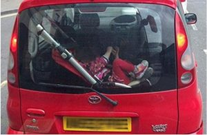 child strapped into pushchair in car boot