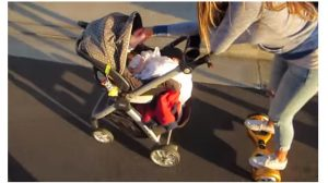 mom on hoverboard feeding baby in stroller