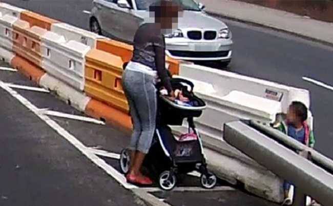 mother with pram and toddler crossing busy motorway