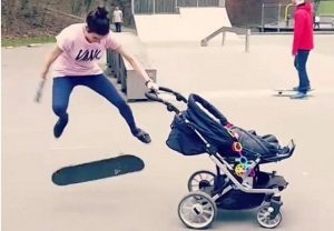 skateboarder does kick-flip while pushing baby stroller